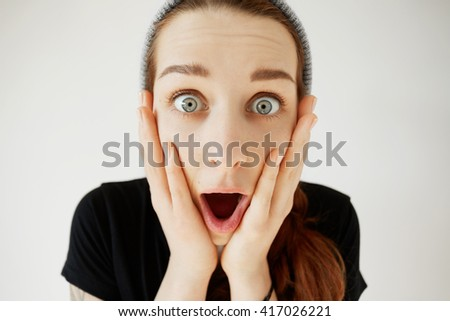 Stunned woman holding hands on her cheeks shocked with unexpected news. Isolated headshot of student girl looking in surprise, mouth wide open, astonished with some incredible news or sale prices - stock photo