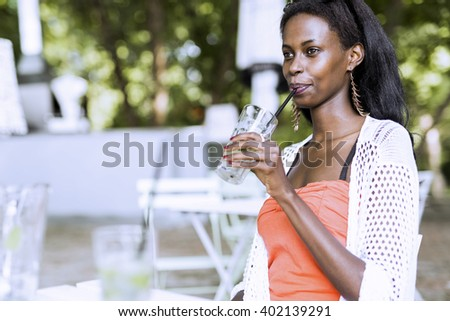 Stunning african woman drinking a refreshing beverage on a summer day