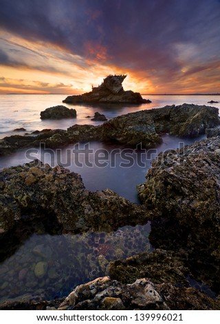 Stunning and colorful sunset exploding on a rocky coastline with tide pools and sea stacks. - stock photo