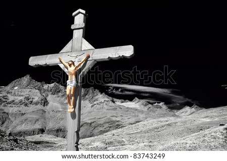 Stunning and dramatic enhanced monochrome cross with jesus christ crucified, in the mountains, above a lake, with high alps in the distance, - stock photo