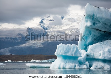 Stunning atmosphere of huge iceberg reflecting in the cool glacial water near the glacier. Glacial Lake jokulsarlon iceland, the Atlantic Ocean. - stock photo