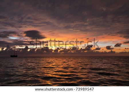 Stunning beautiful Ocean Sunset with Sailboat, yacht, in the background and a cloudy colored sky in the Similan Islands, National Marine Park, Thailand.