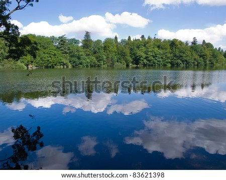 Stunning beautiful reflection of trees and clouds in a lake great mirror effect