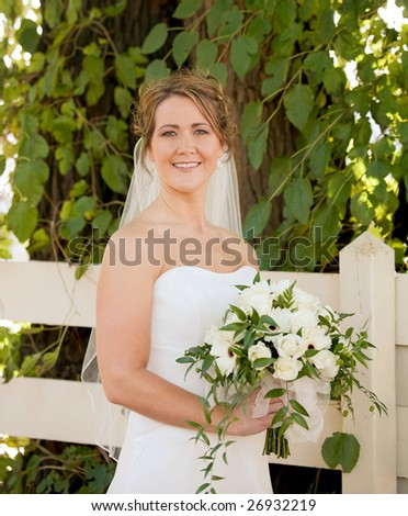 Stunning Bride Holding a Bouquet in Front of a White Fence - stock photo