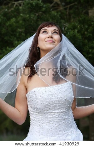 Stunning bride with lovely smile looking up in a beautiful wedding dress