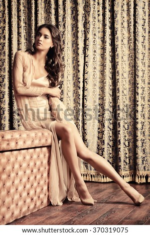 Stunning brunette lady wearing elegant evening dress in a room with classic vintage interior. Fashion shot.  - stock photo