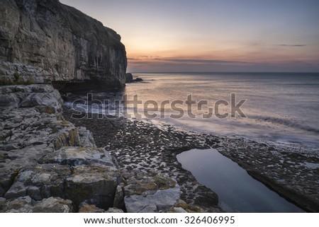 Stunning coastal landscape with long exposure waves crashing onto rocks at sunrise - stock photo