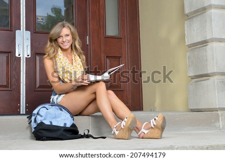 Stunning female college student sitting outside building with book on lap smiling at viewer - back to school themed - stock photo