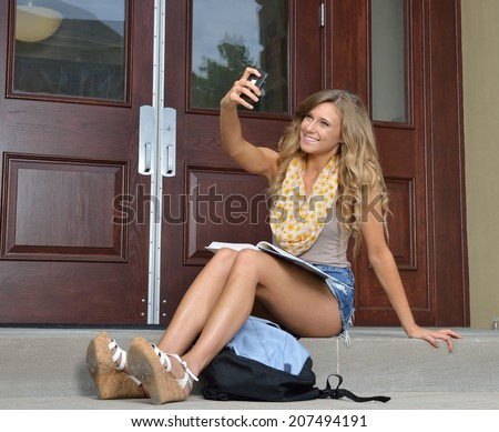 Stunning female college student sitting outside building with book on lap taking a selfie - stock photo