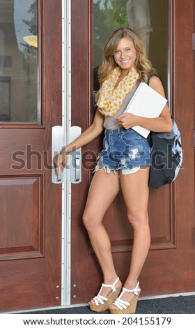 Stunning female college student stands outside building with her books - ready to enter building - back to school - stock photo