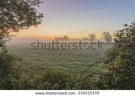 Stunning foggy Autumn  sunrise English countryside landscape image - stock photo