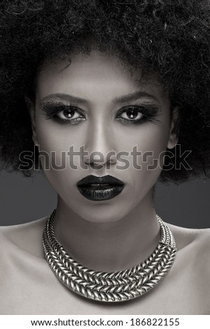 Stunning glamorous African American woman wearing dark makeup looking at the camera with parted lips close up face portrait