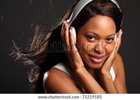 Stunning happy black woman wearing headphones - stock photo
