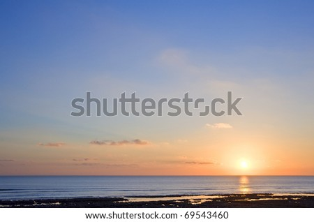 Stunning image of deep sunset over calm smooth sea with vibrant colors and plenty of copy space - stock photo