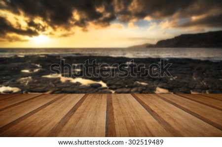 Stunning landscape ocean at sunset dramatic clouds with wooden planks floor - stock photo