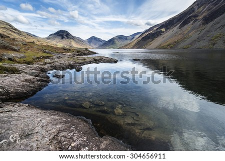Stunning landscape of Wast Water and Lake District Peaks on Summer day reflected in perfect lake - stock photo