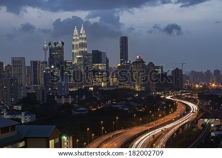 Stunning light trail from the busy highway traffic and Kuala Lumpur twin towers as a background - stock photo