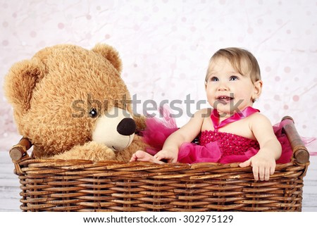 Stunning little baby girl sitting in th wicker basket with big teddy bear - stock photo