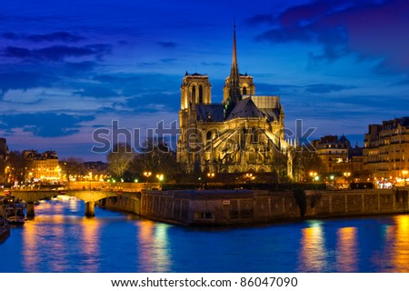 Stunning Notre-Dame Cathedral (1163) and Parisian apartments along the banks of the river Seine, Paris, France illuminated at night. - stock photo
