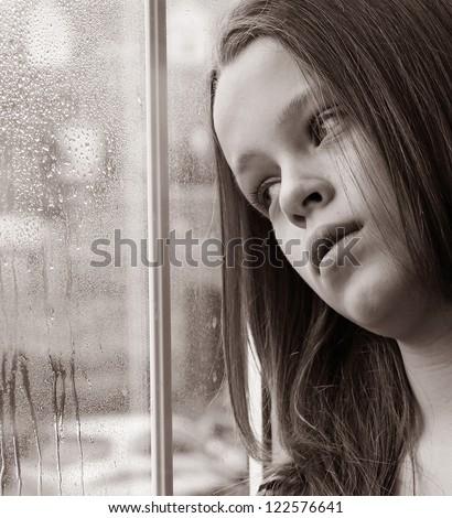 Stunning photo of a young girl gazing through a rainy window - stock photo