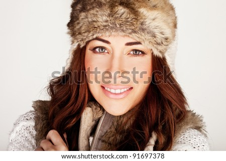 Stunning Redhead In Winter Fur Hat with subtle make-up and lovely smile. - stock photo