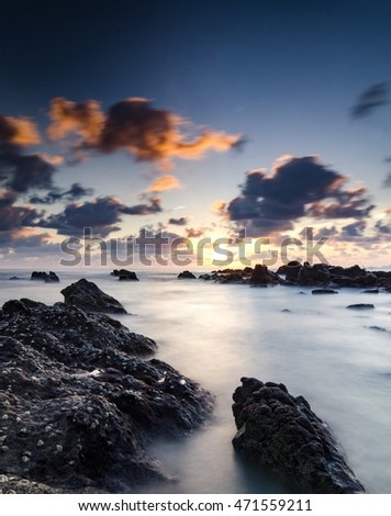 Stunning scenery and magical light of Pandak beach Located in Terengganu,Malaysia during sunrise with waves flowing over the boulders