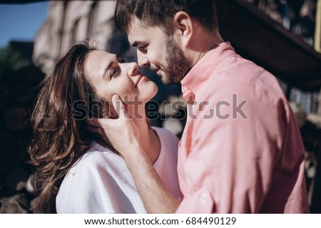 Stunning sensual outdoor portrait of young stylish fashion couple in love. Woman and man embrace and want to kiss each other. They are smiling and looking to each other