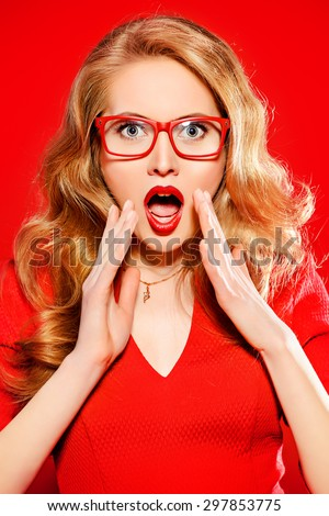 Stunning sensual woman with magnificent blonde hair wearing red dress and elegant red glasses. Beauty, fashion. Optics, eyewear.