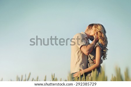 stunning sensual young couple in love posing in summer field, happy lifestyle concept - stock photo