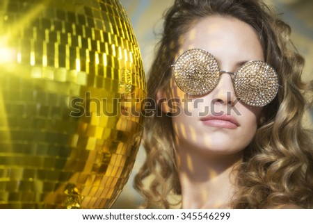 stunning sexy disco woman with gold crystal sunglasses, surrounded by gold disco balls