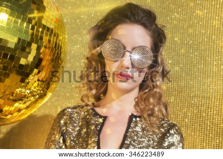 stunning sexy disco woman with gold crystal sunglasses, surrounded by gold disco balls - stock photo