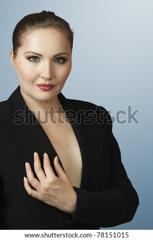 Stunning sexy woman in black suit looking to camera - stock photo