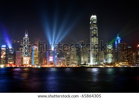 Stunning sight seeing of the Victoria harbor in Hong Kong illuminated at nighttime with futuristic buildings and colorful lights. - stock photo