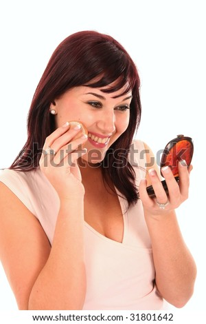 Stunning smiling brunette woman applying make up to her face - stock photo