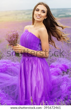 Stunning smiling woman is wearing fashion purple dress holding bouquet of flowers on the nature in lavender field - stock photo