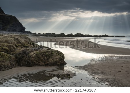 Stunning sun beams bursting from sky over empty yellow sand beach landscape - stock photo