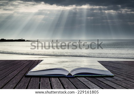 Stunning sun beams bursting from sky over empty yellow sand beach landscape conceptual book image - stock photo
