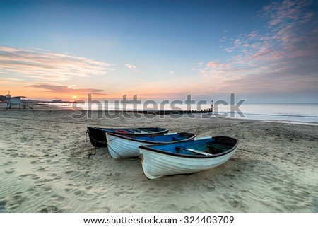 Stunning sunrise over a row of fishing boats on Bournemouth beach in Dorset, with the pier in the far distance - stock photo