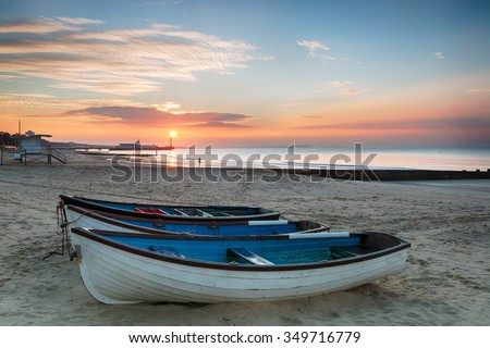 Stunning sunrise over fishing boats at Durley Chine on Bournemouth beach in Dorset with the sun rising over the end of the pier - stock photo