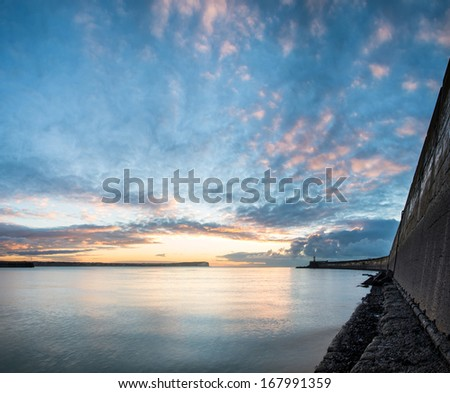 Stunning sunrise over ocean with lighthouse and harbor wall - stock photo