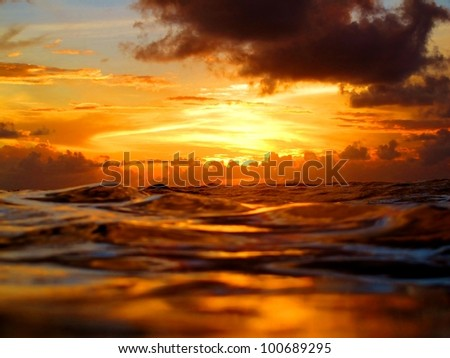 Stunning sunset during a night dive, image features colorful setting and reflections on water - stock photo