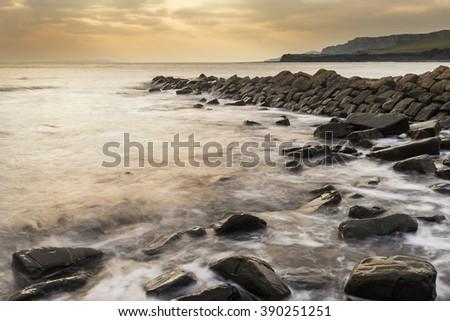 Stunning sunset landscape image of rocky coastline in Dorset England - stock photo