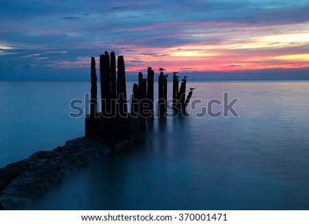 Stunning sunset on the beach of the Caribbean Sea with the ruined pier