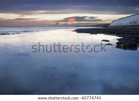 Stunning sunset over motion blurred sea at low tide with cliffs - stock photo