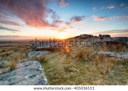 Stunning sunset over slabs of granite rocks at the top of Alex Tor near St Breward on Bodmin Moor in Cornwall - stock photo