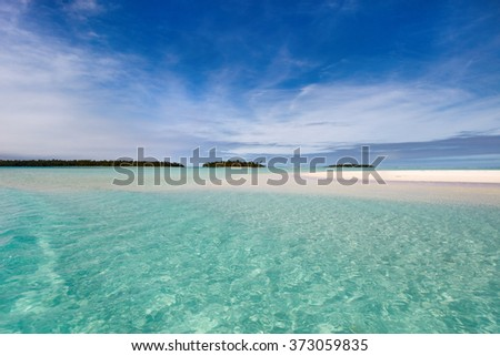 Stunning tropical lagoon and exotic islands with palm trees, white sand, turquoise ocean water and blue sky at Cook Islands, South Pacific - stock photo