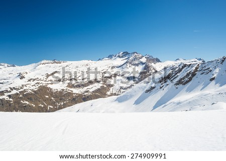 Stunning view of high mountain peaks arising from the alpine arc, in a bright sunny day of spring and lot of candid snow in the foreground. M. Gran Paradiso (4061 m) in the background, Italy. - stock photo