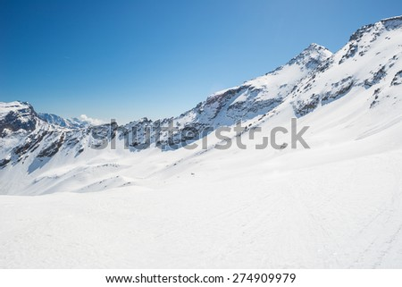 Stunning view of high mountain peaks arising from the italian alpine arc, in a bright sunny day of spring and lot of candid snow in the foreground. - stock photo