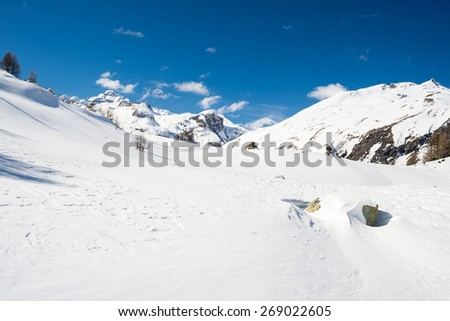 Stunning view of high mountain peaks in the italian alpine arc, in a bright sunny day and lot of candid snow. Ski resort of La Thuile and La Rosiere, on the border Italy France. - stock photo