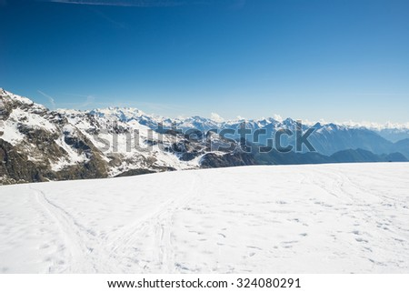 Stunning view of high mountain peaks in the italian alpine arc, in a bright sunny day of winter. Candid snowy slope in the foreground and the majestic Monte Rosa massif in the distance (over 4000 m). - stock photo